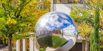 photo of silver spherical outdoor sculpture on ANU grounds